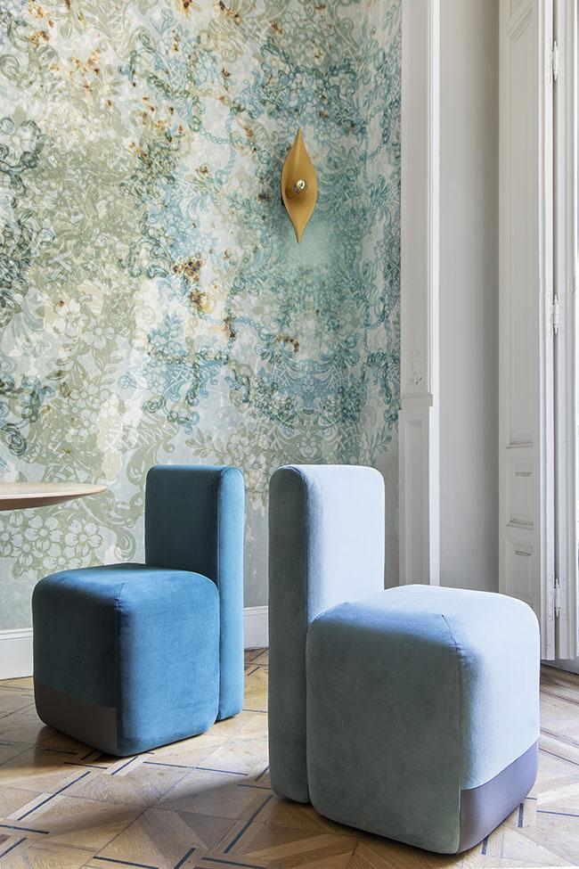 Con el fondo de un papel pintado diseñdo a medida para el espacio, butacas azules de Piero Lissoni Season Chair que edita Viccarbe