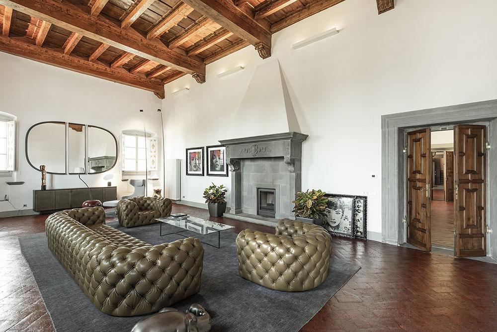 Vista del salón principal presidido por una chimenea restaurada y por un sofá y sillones de cuero